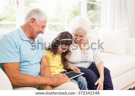 Grandparents using tablet with their granddaughter at home - stock photo