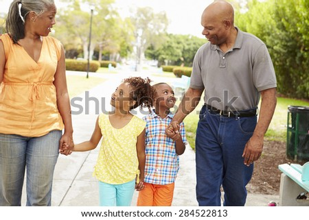 Grandparents Walking Grandchildren In Park