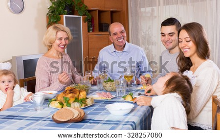 Grandparents with adult children and little grandchildren at the festive table in light room