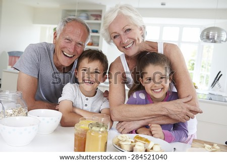 Grandparents With Grandchildren Eating Breakfast In Kitchen - stock photo