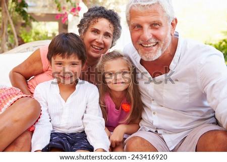 Grandparents With Grandchildren Sitting On Seat In Garden - stock photo
