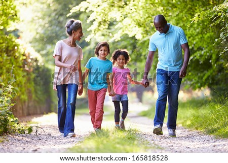 Grandparents With Grandchildren Walking Through Countryside - stock photo