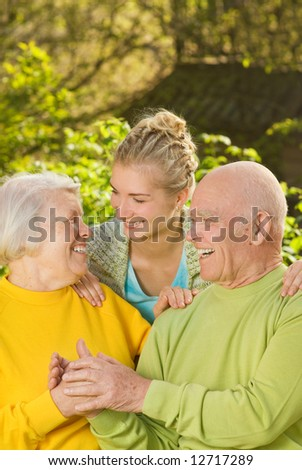 Grandparents with granddaughter outdoors - stock photo