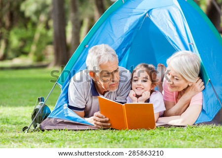 Grandparents with granddaughter reading book in tent at park - stock photo