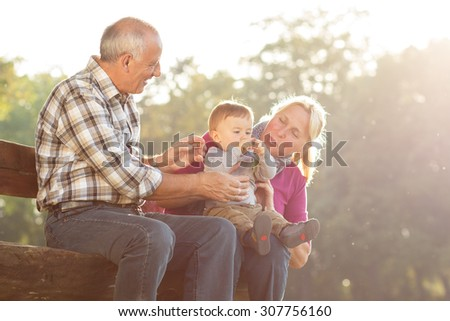 Grandparents with grandson enjoying the sunny autumn day in park - stock photo