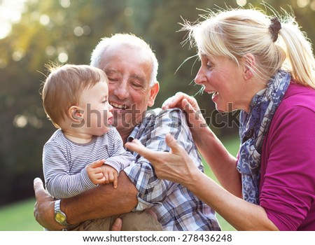 Grandparents with grandson enjoying the sunny day in park. - stock photo