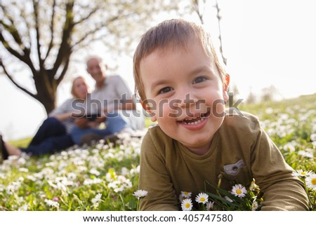 Grandparents with grandson enjoying the sunny spring day outdoors. Portrait of the little boy looking at camera. - stock photo