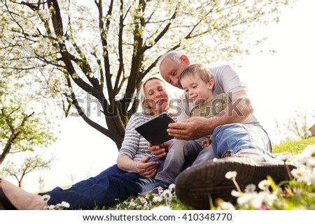 Grandparents with grandson enjoying the sunny spring day outdoors. They are looking something on tablet. - stock photo