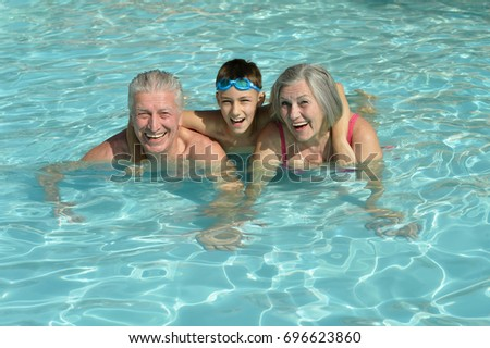 grandparents with grandson in swimming pool