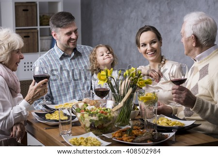 Grandparents with their children and granddaughter sitting beside table during family dinner - stock photo