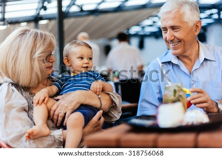 Grandparents With Their Grandson Spending Lovely Time At Cafe - stock photo