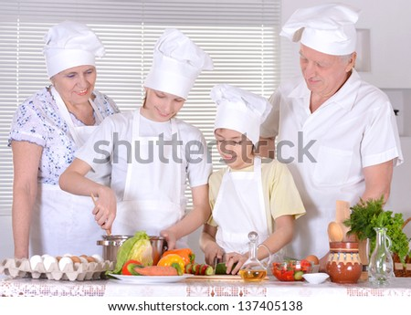 grandparents with two boys are preparing dinner together - stock photo