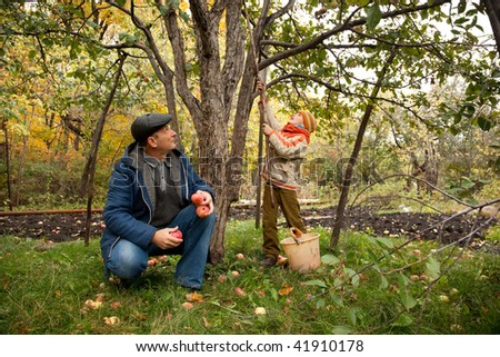 Grandson and grandfather neat the apple tree in autumnal garden