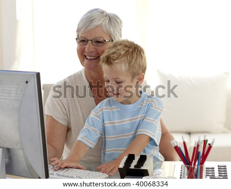 Grandson and grandmother using a computer at home - stock photo