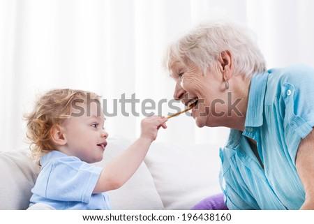 Grandson and his grandma eating together, horizontal - stock photo