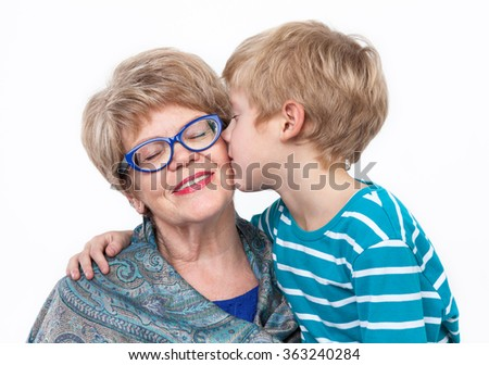 Grandson kissing happy grandmother on the cheek, white background - stock photo