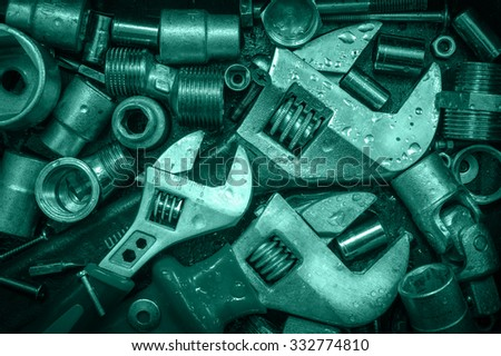 Grange background with wet tools and bolts. Adjustable wrenches, screws, nuts. Toned. - stock photo