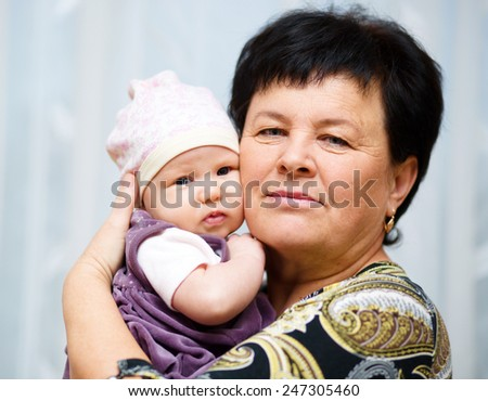 Grangmother holds cute 3 months baby - stock photo