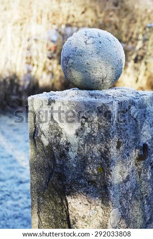 granite ball on a pedestal covered with frost, vertical - stock photo