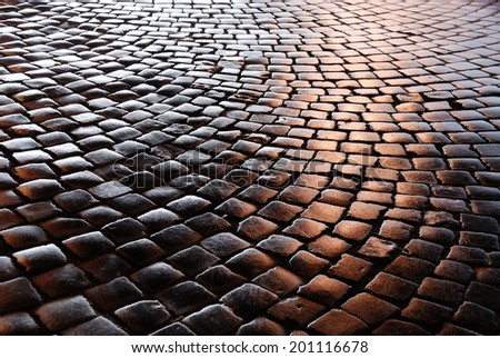 Granite cobblestones of the Belgian block pavement are photographed at night. - stock photo