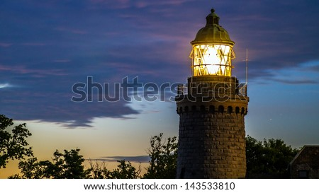 Granite lighthouse by during a Scandinavian midsummer midnight on the island of Bornholm from the side