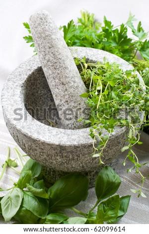 Granite mortar with fresh herbs, still life. - stock photo