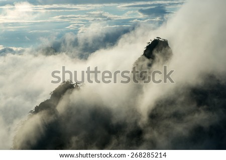 Granite mountain peak in a sea of clouds during the blue hour of sunrise, Huangshan (Yellow Mountains), Anhui Province, China - stock photo