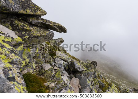 Granite rock formations, fog and clouds in the Romanian Alps