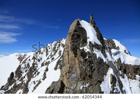 granite rock on a background of snow-capped peaks and blue sky