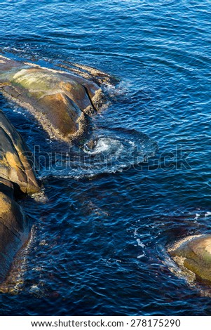 Granite rocks in the sea with swirling currents - stock photo