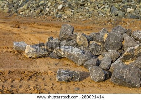 Granite stones placed on the ground gravel pile with traces wheel vehicles. - stock photo