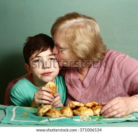 grannie in glasses hug her holding pie  grandson close up portrait - stock photo