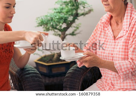 Granny and granddaughter spending teatime together - stock photo