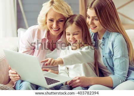 Granny, her daughter and granddaughter are using a laptop and smiling while sitting on sofa at home - stock photo