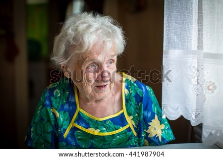 Granny is sitting near the window in the kitchen.