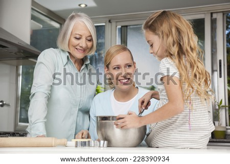 Granny, Mother and daughter baking in kitchen - stock photo