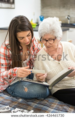 Granny sitting on couch next to her granddaughter and looking through photo album. - stock photo