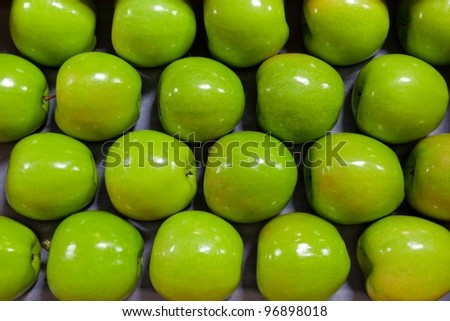 Granny Smith Apples in a fruit packing warehouse - lined up on a packing tray - stock photo