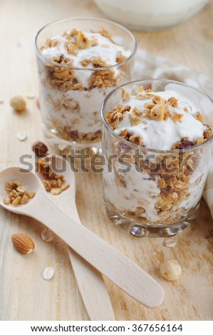 Granola baked with nuts and honey and homemade yogurt for breakfast on wooden table