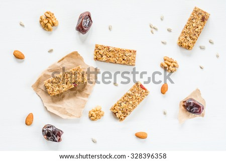 Granola bar or energy bar with oats, dates and nuts on white wooden background, top view. Snack for yoga, fitness and sports people - stock photo