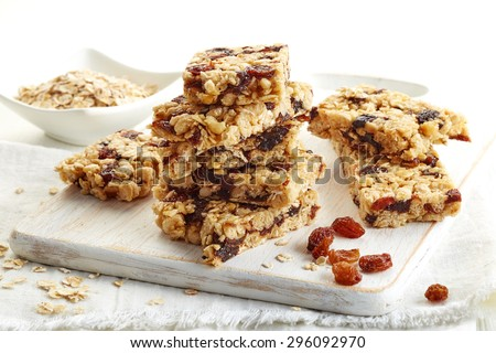 Granola bar with raisins on white wooden background - stock photo
