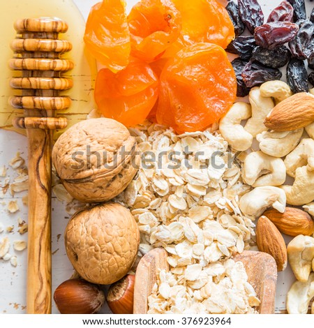 Granola bars ingredients on white wood background, top view