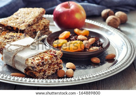 Granola bars on plate with nuts and dried fruits on wooden background - stock photo