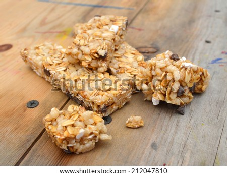 Granola bars with chocolate on tablecloth  - stock photo