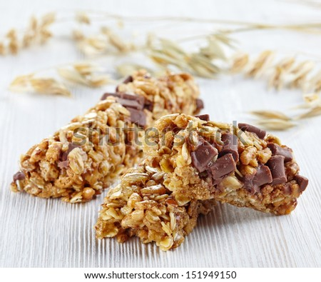 Granola bars with chocolate on white wooden background - stock photo