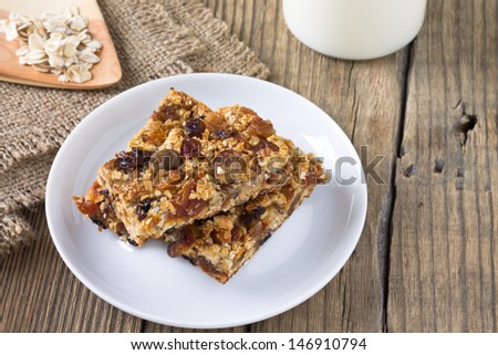 Granola bars with nuts and dried fruits, glass of milk on wooden background - stock photo