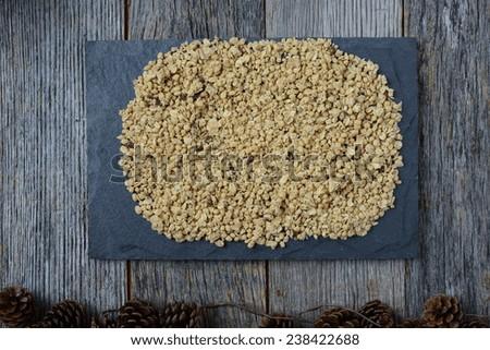 Granola Covering Dark Grey Slate with Pinecones on Dark Wood Background - stock photo