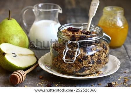 Granola from rye and oat flakes with dried cranberries and coconut in a glass jar on wooden table. - stock photo