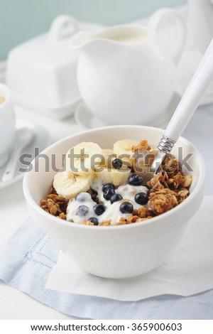 Granola from several types of cereals with fresh blueberries and banana for breakfast