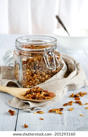 Granola in a glass jar on a white wooden background, selective focus - stock photo